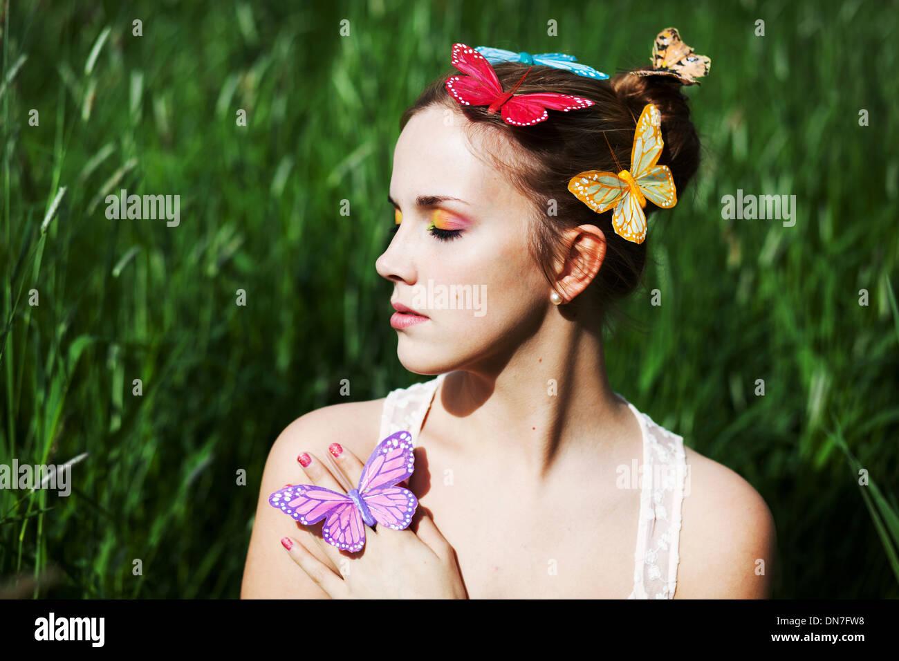 Junge Frau mit geschlossenen Augen und künstliche Schmetterlinge Stockbild