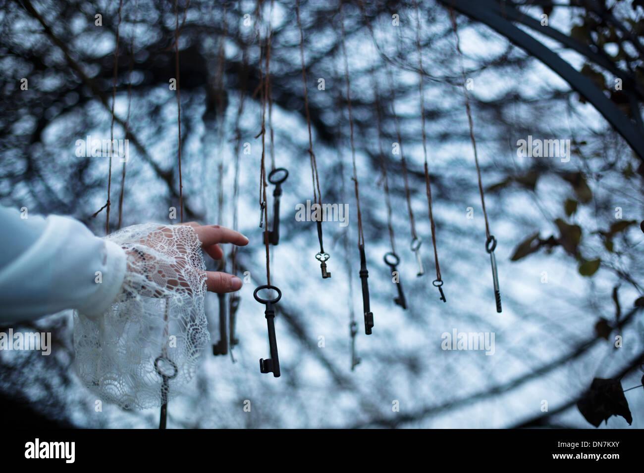 Frau greift nach Schlüssel in einem Baum Stockbild