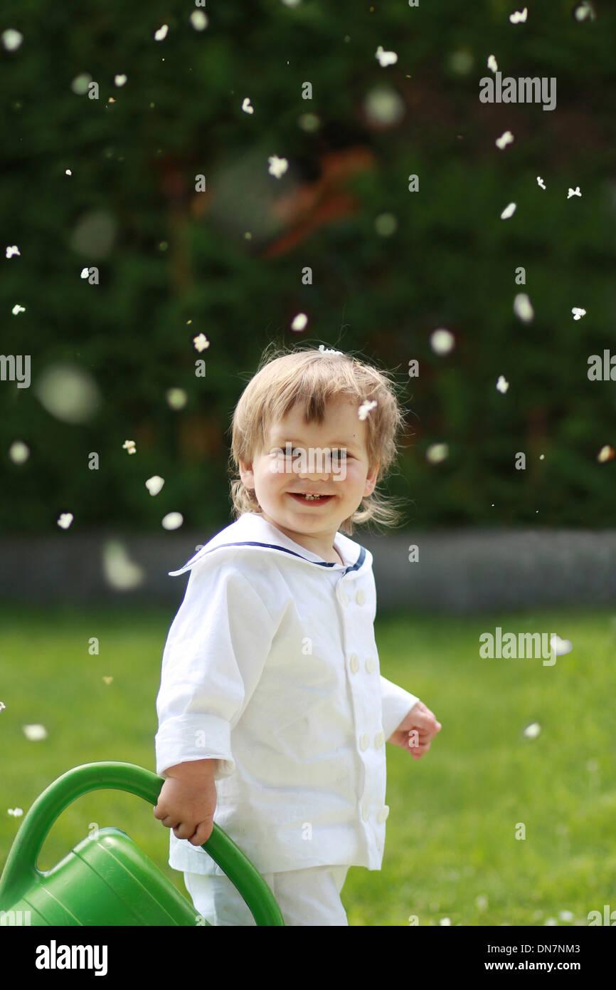 Kleiner Junge mit Gießkanne auf einer Wiese Stockbild