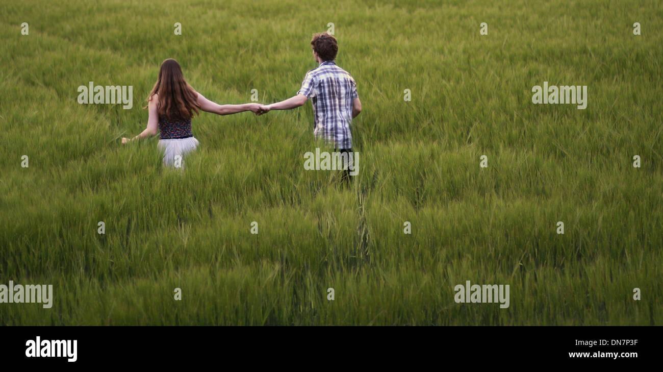 Junges Paar Spaziergänge hand in hand durch Kornfeld Stockbild