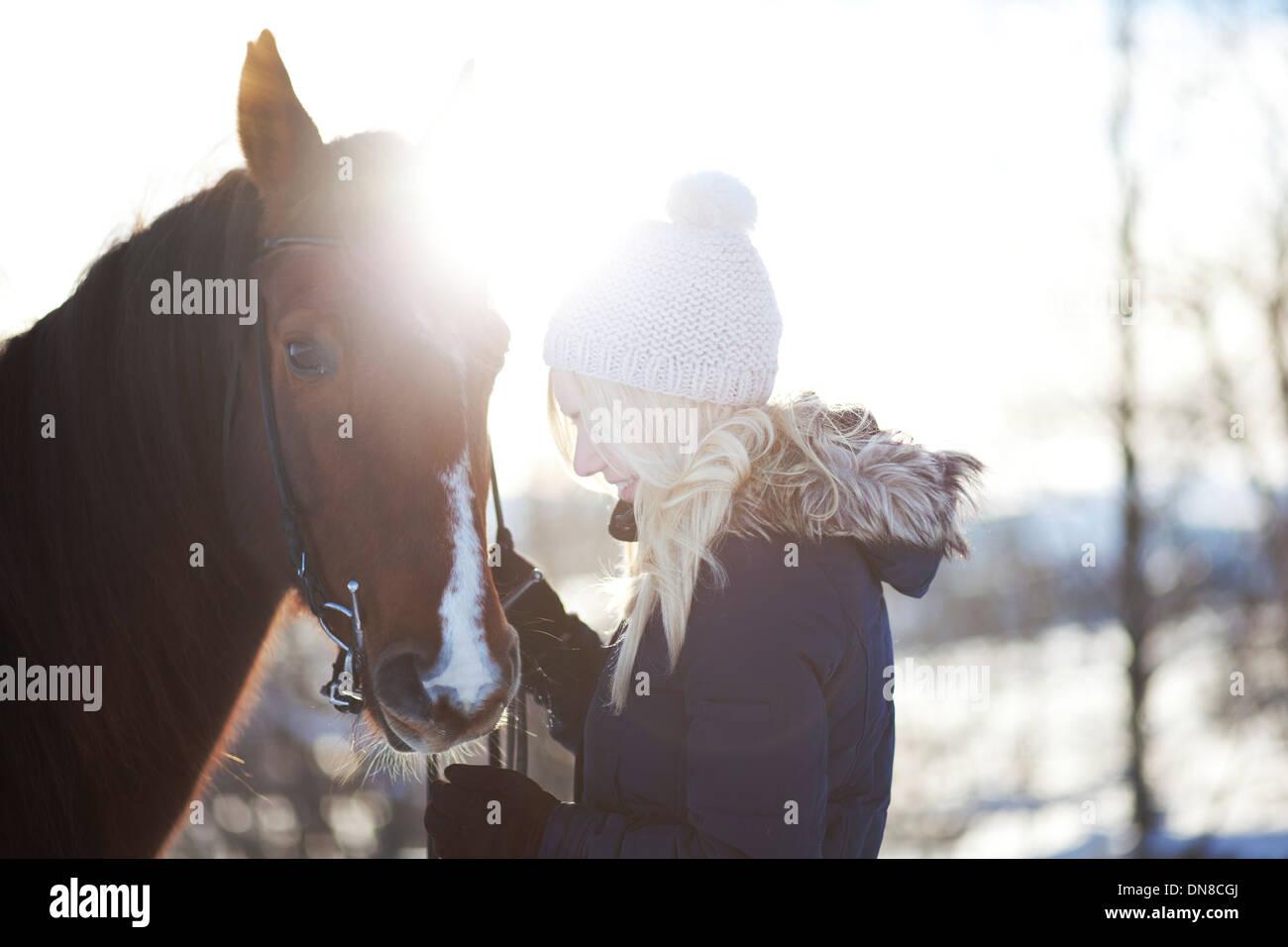 Junge Frau mit Pferd im winter Stockbild