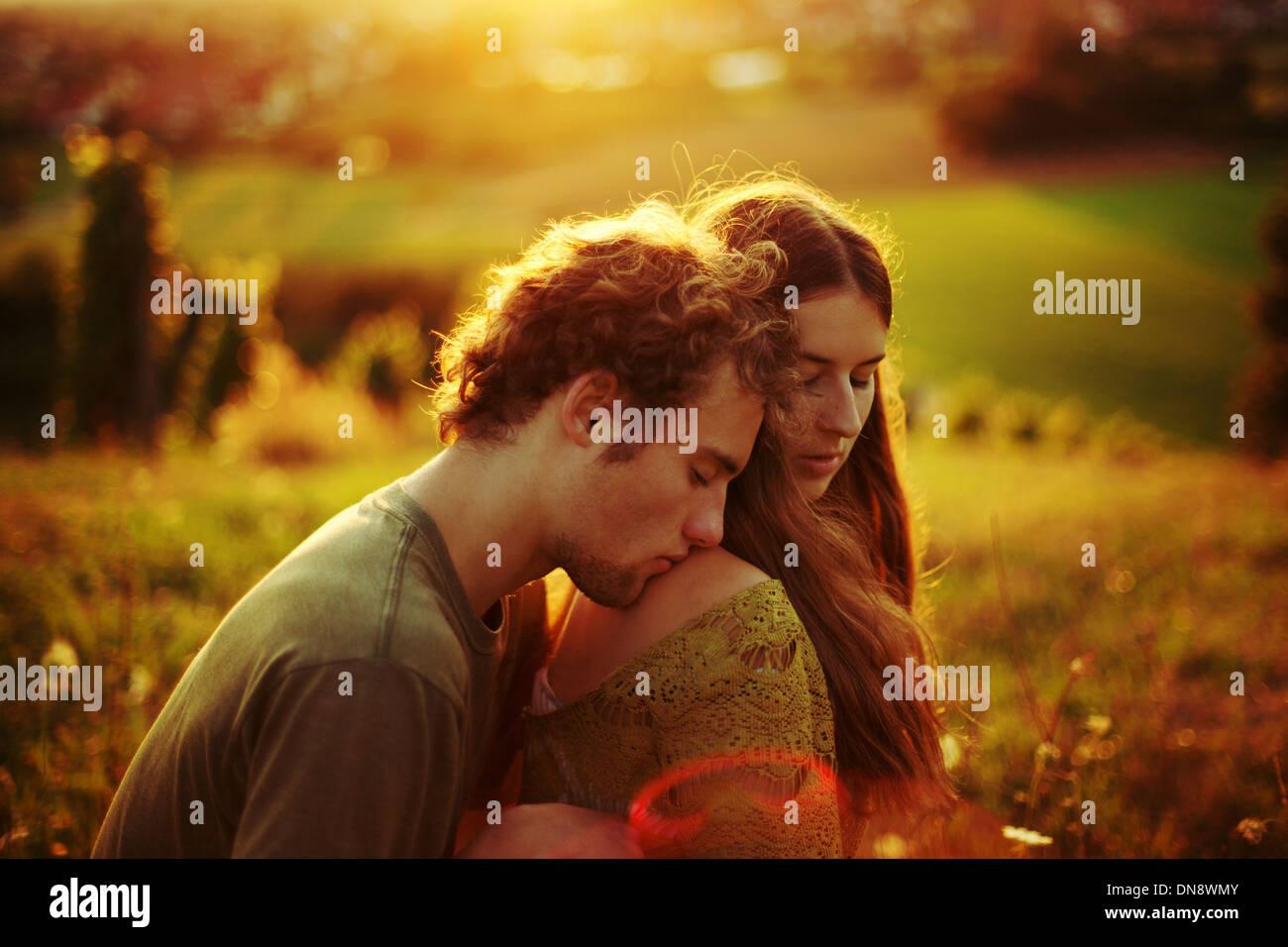 Junges Paar in Liebe umarmen auf einer Wiese Stockbild