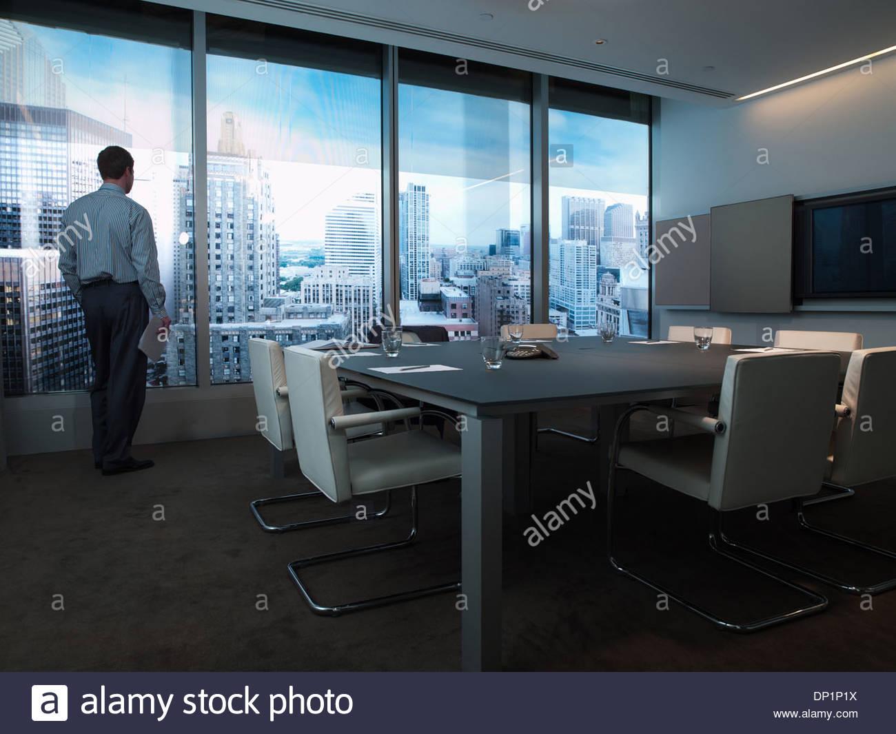 Geschäftsmann am Fenster des Konferenz-Zimmer mit Blick auf Stadt Stockbild