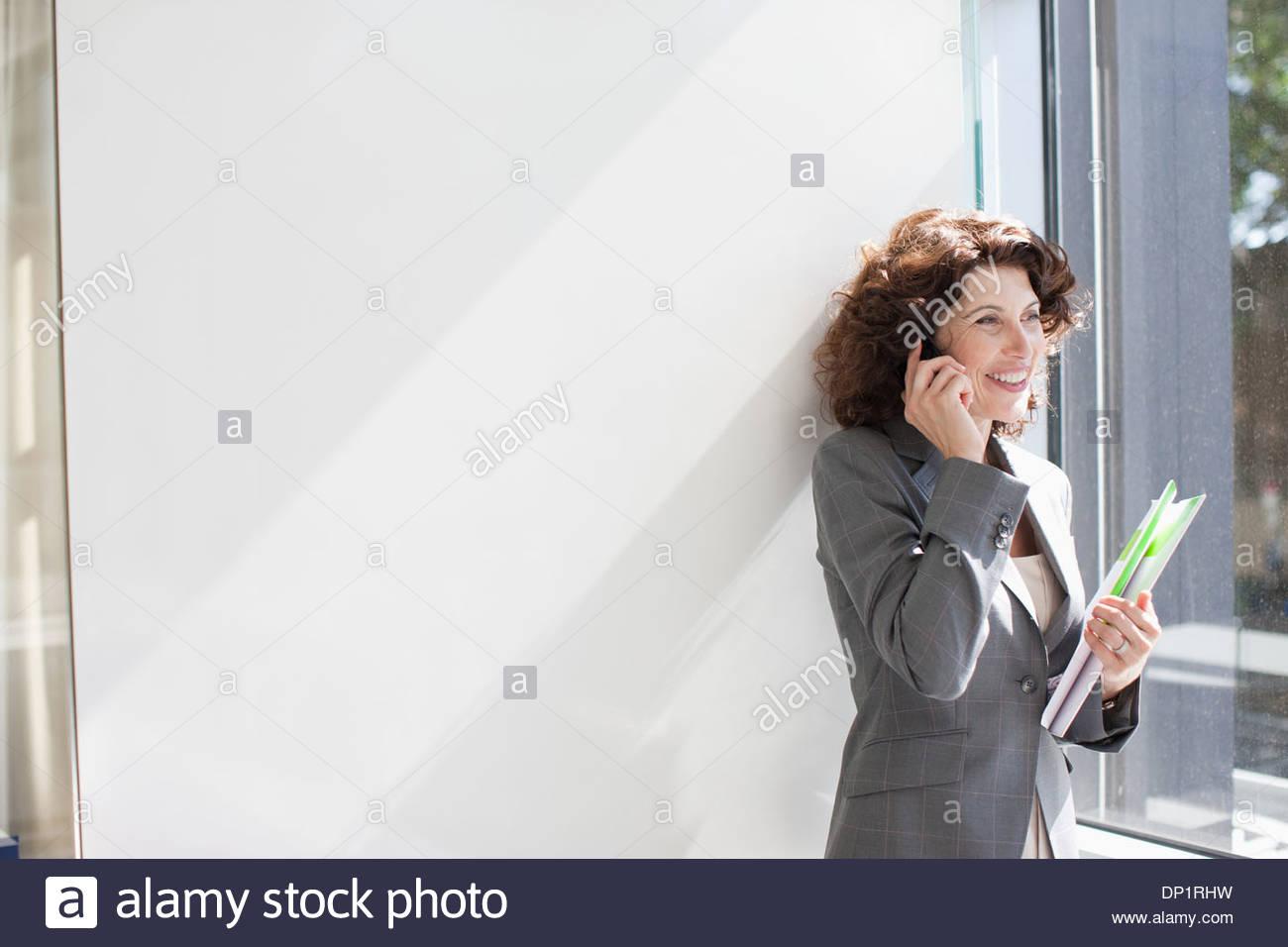 Geschäftsfrau, reden über Handy durch Fenster Stockbild