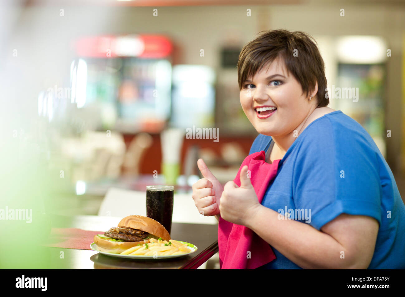 Junge Frau in Café mit ungesunde Mahlzeit Stockbild