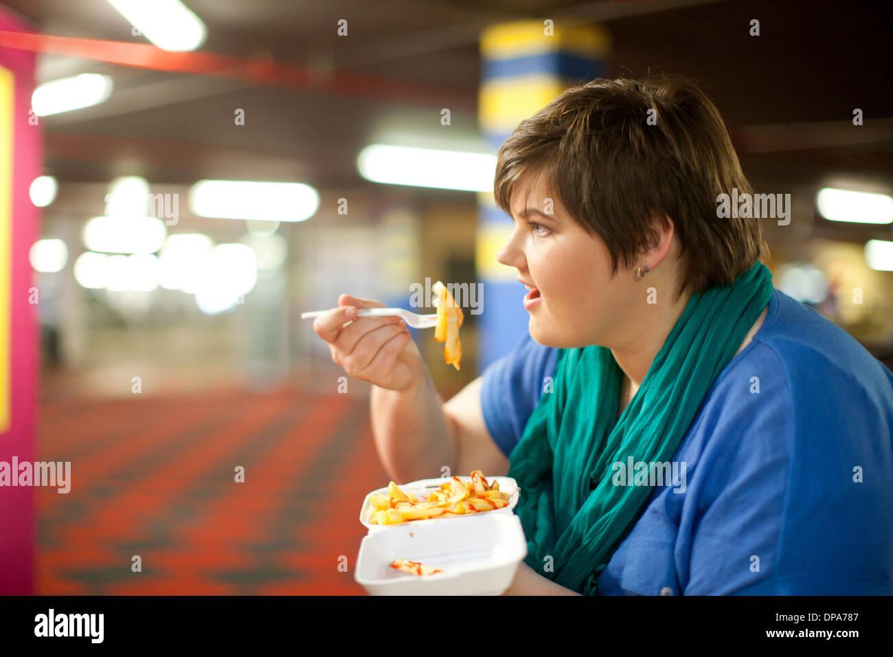 Junge Frau Essen zum Mitnehmen frites Stockbild