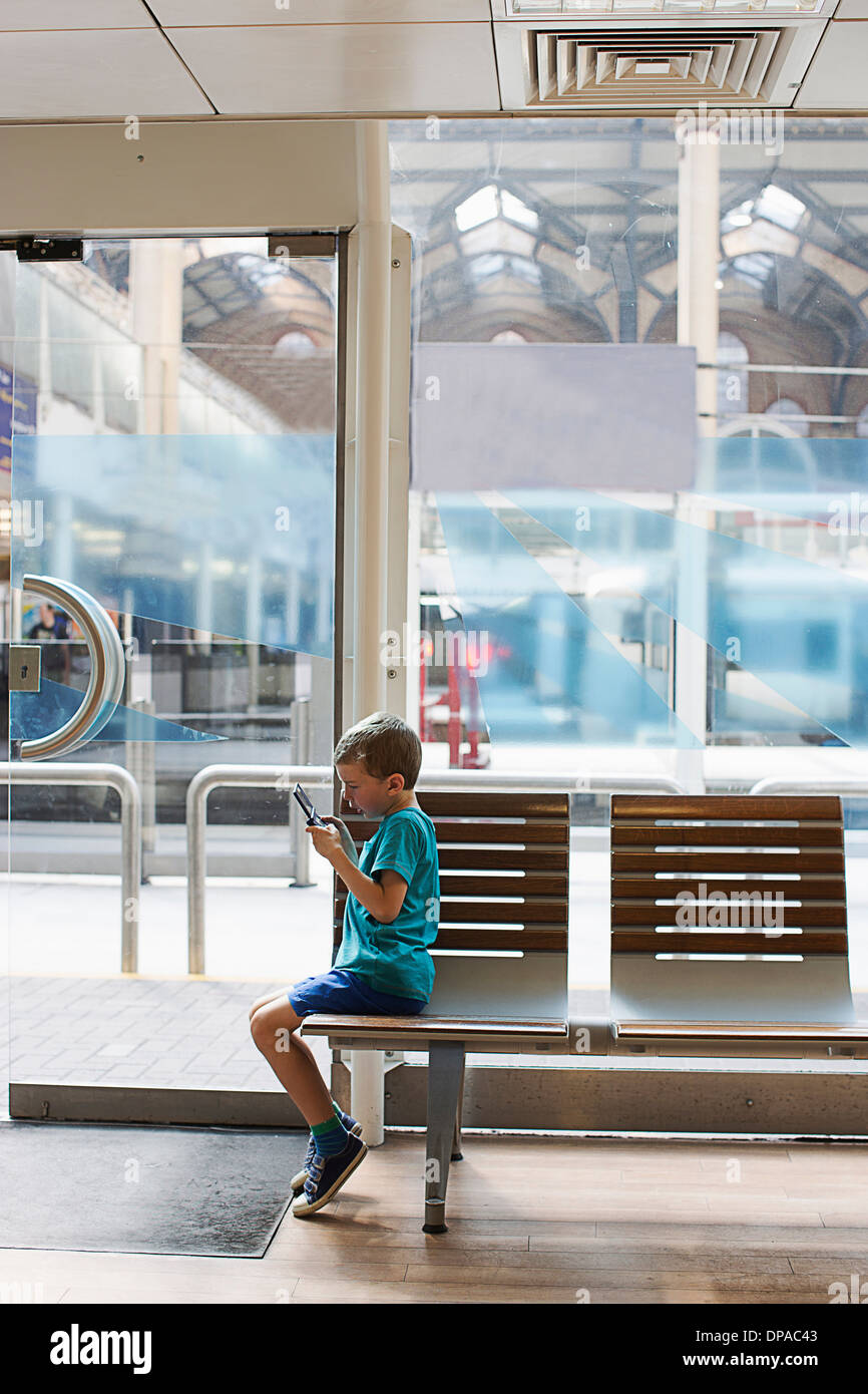 Kleiner Junge im Zug Bahnhof Wartezimmer elektronisches Spiel Stockbild