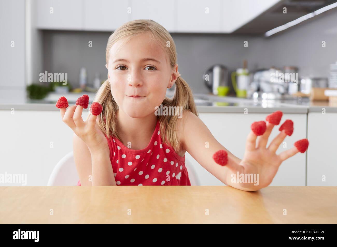 Mädchen essen Himbeeren von Fingern Stockbild