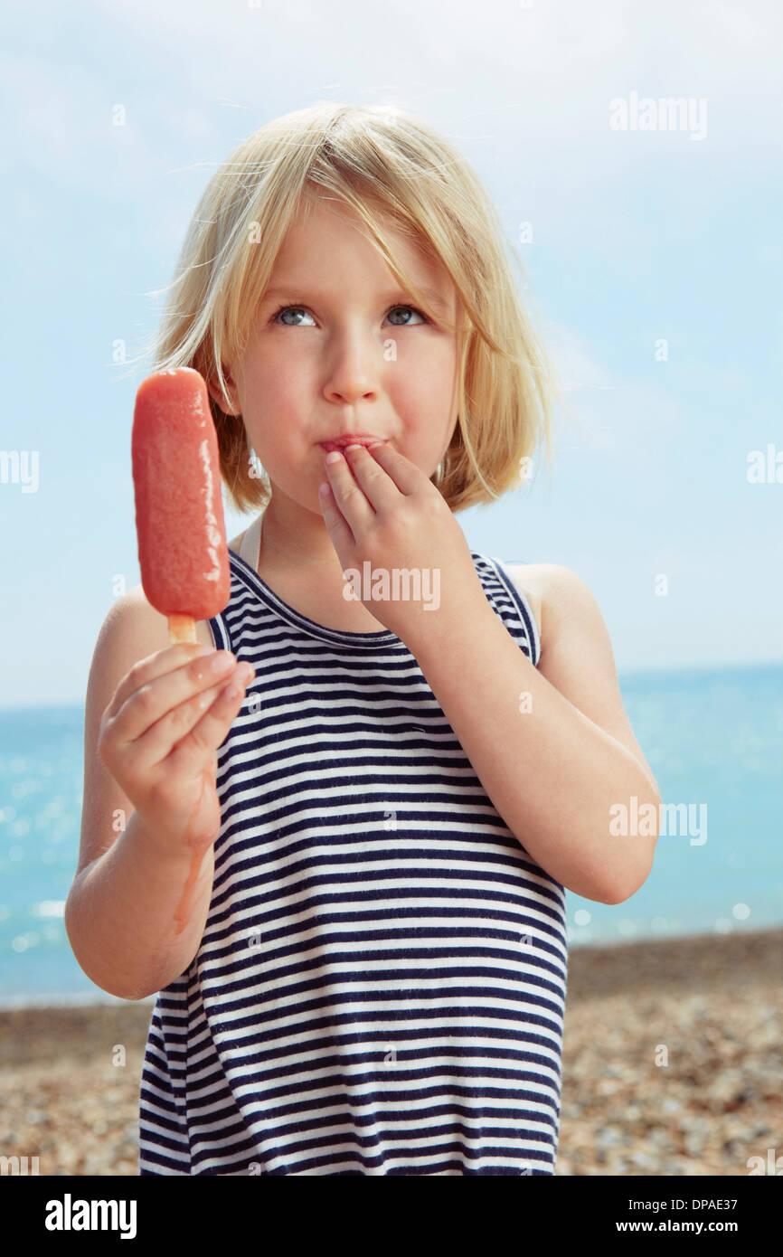 Kind mit Fingern auf Lippe halten Eis am Stiel Stockbild