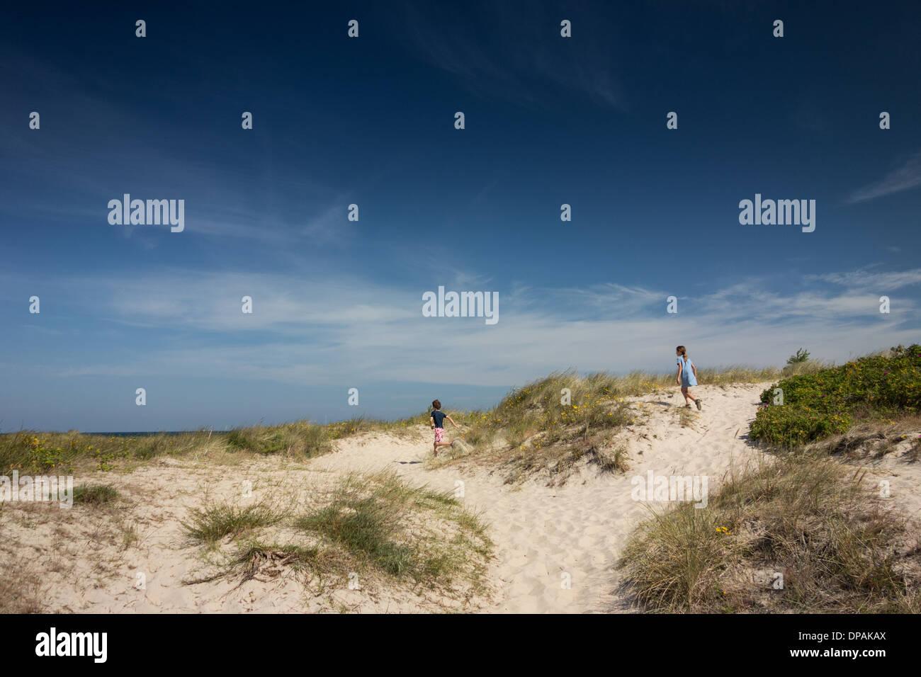 Bruder und Schwester läuft über Sanddünen Stockbild