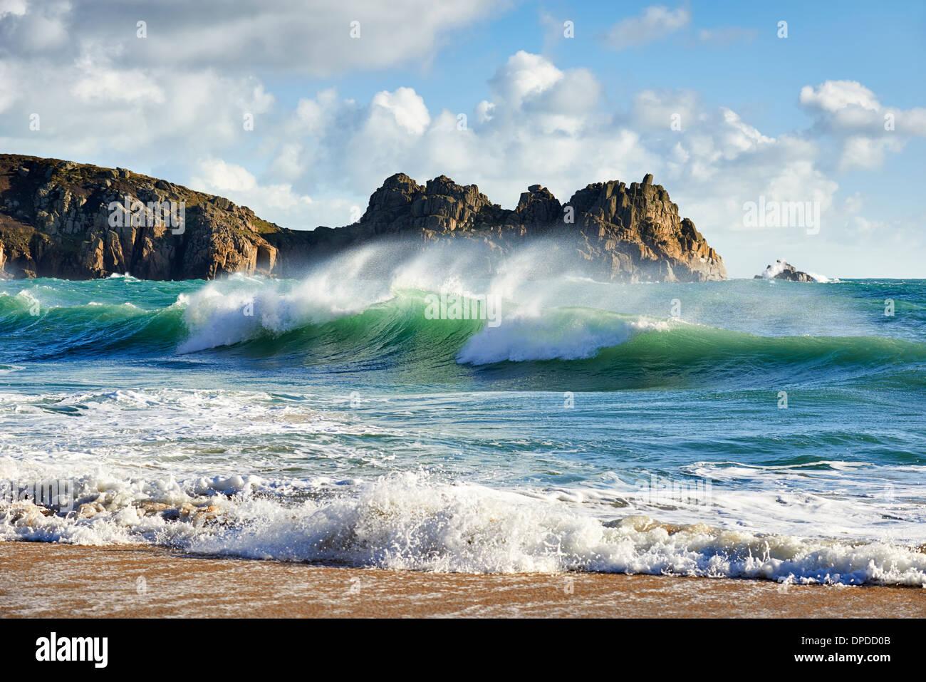 Ein curling Welle brechen im Porthcurno Beach, West Cornwall Stockbild