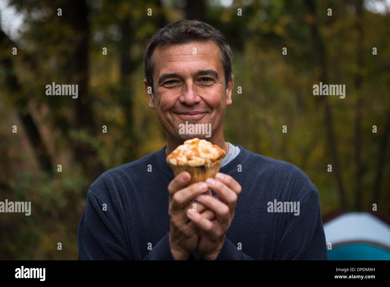 Reifer Mann im Wald hält cupcake Stockbild