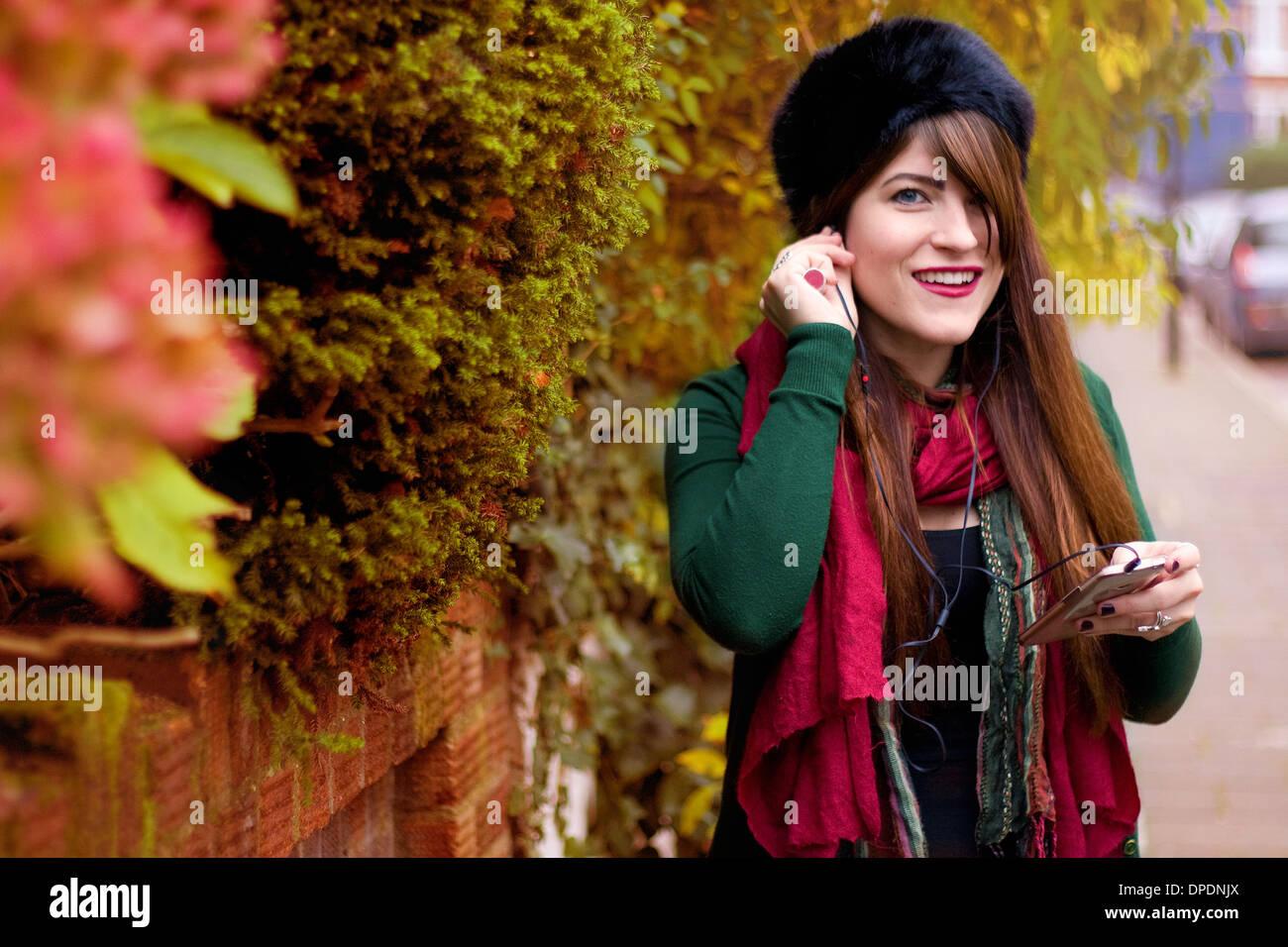 Junge Frau tragen Winterkleidung, mit smartphone Stockbild