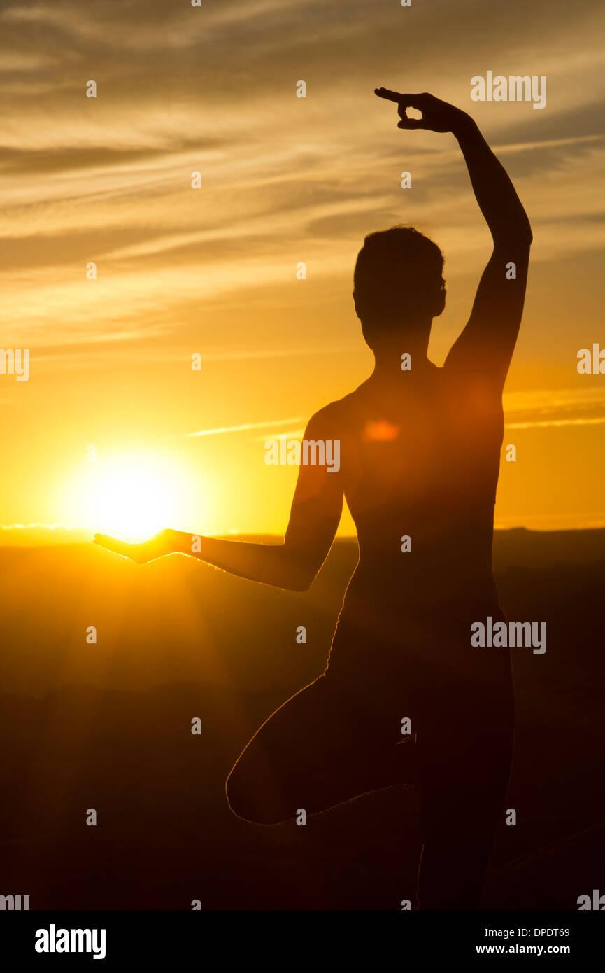 Junge Frau beim Yoga im Sonnenlicht, Moab, Utah, USA Stockbild