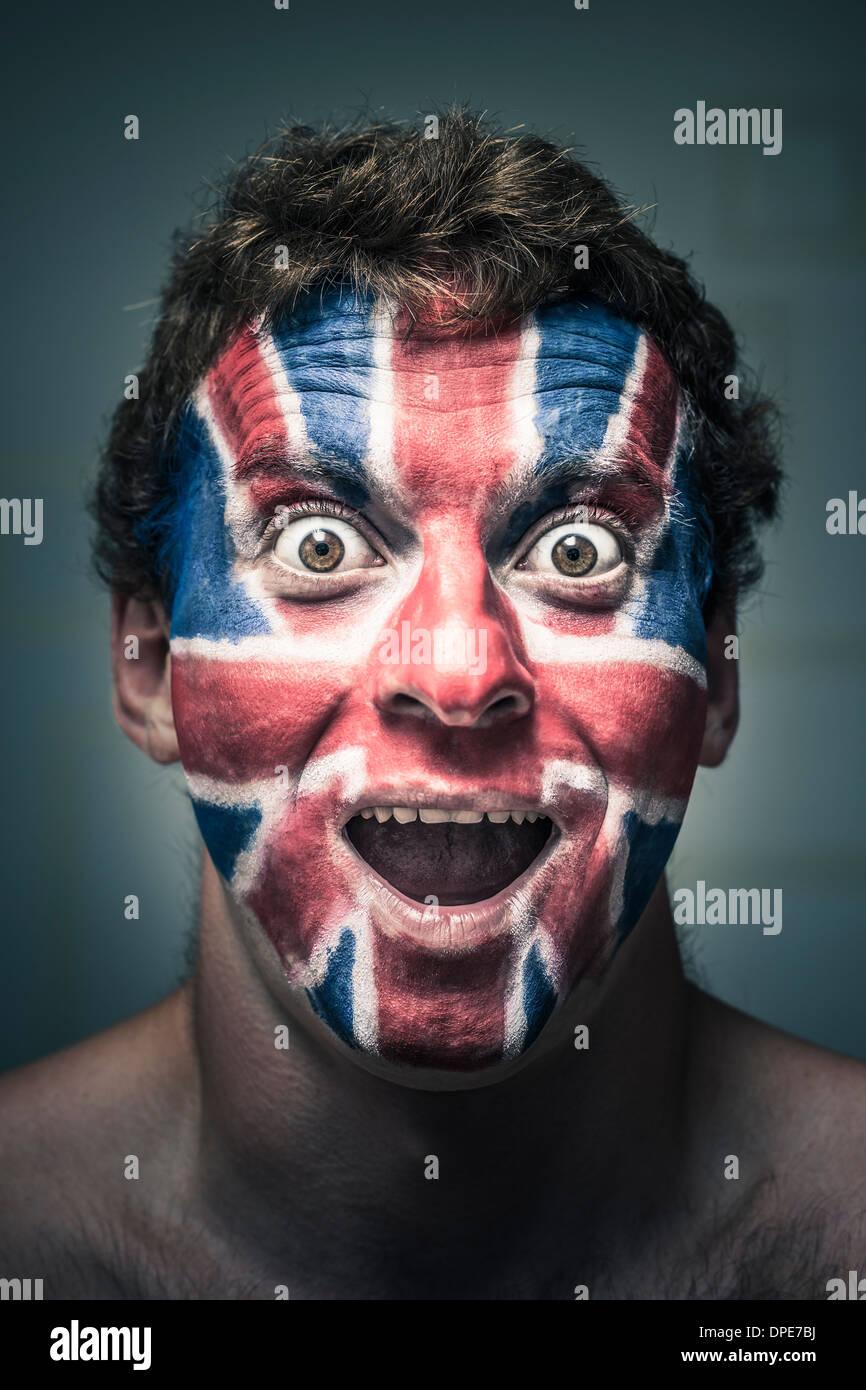 Porträt von schockiert Mann mit britischer Flagge gemalt auf Gesicht. Stockbild