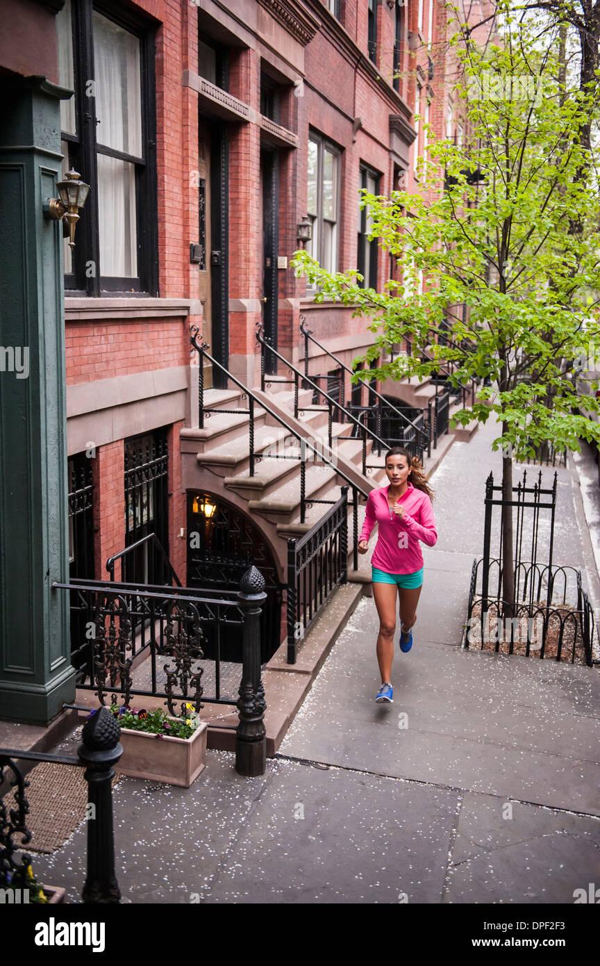 Frau, jogging am Bürgersteig Stockbild
