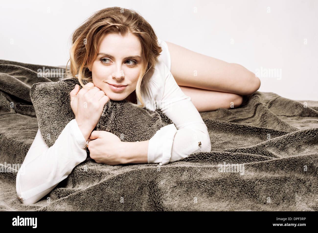 Frau umklammert Kissen im Bett Stockbild
