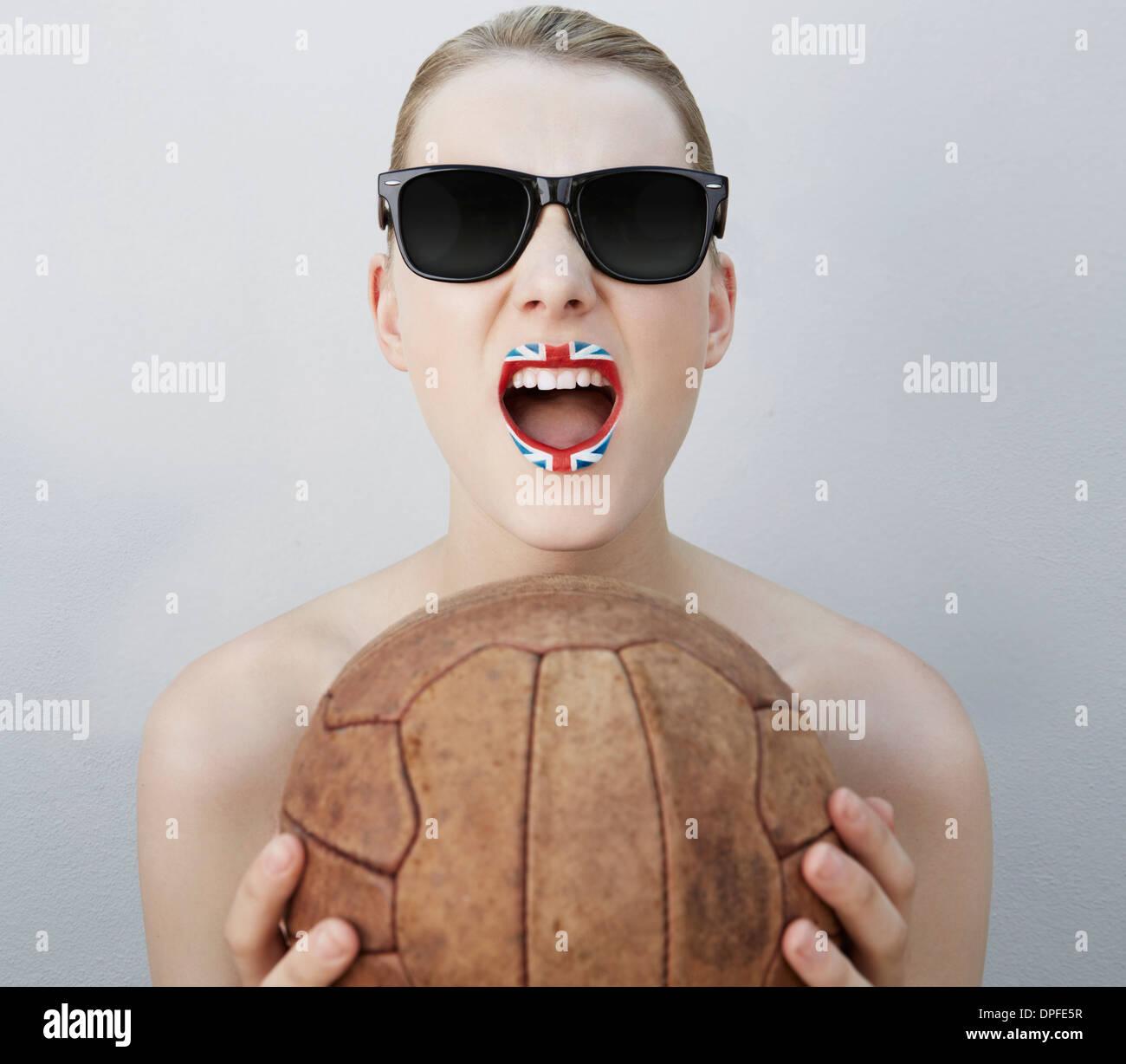 Frau mit britischer Flagge Lippenstift, mit Fußball Stockbild