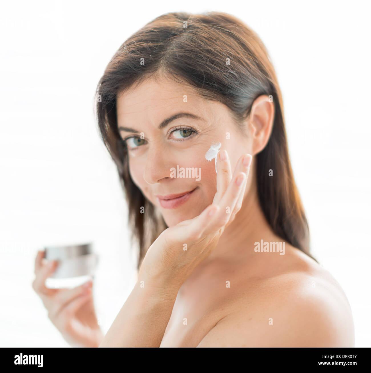attraktive Frau in den Vierzigern auftragen Creme Stockbild