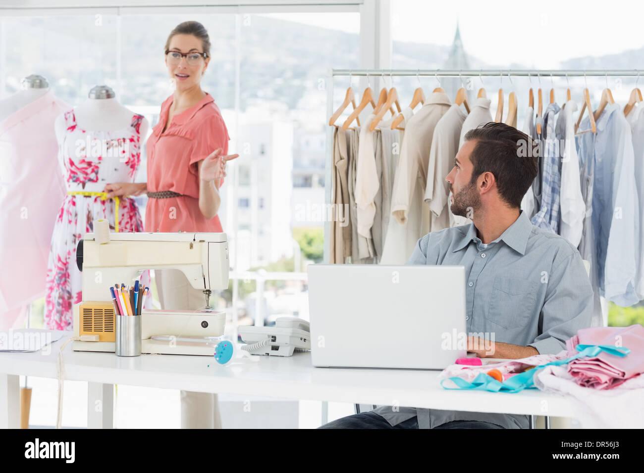 Mann mit Laptop mit Modedesigner arbeiten im studio Stockbild