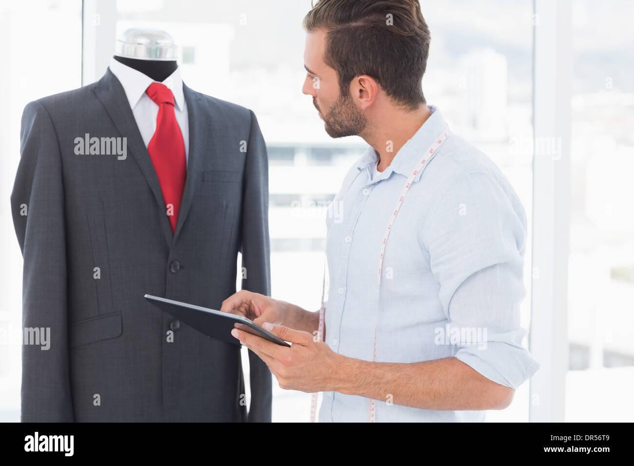 Konzentrierte Modedesigner mit digital-Tablette betrachten Anzug auf dummy Stockbild