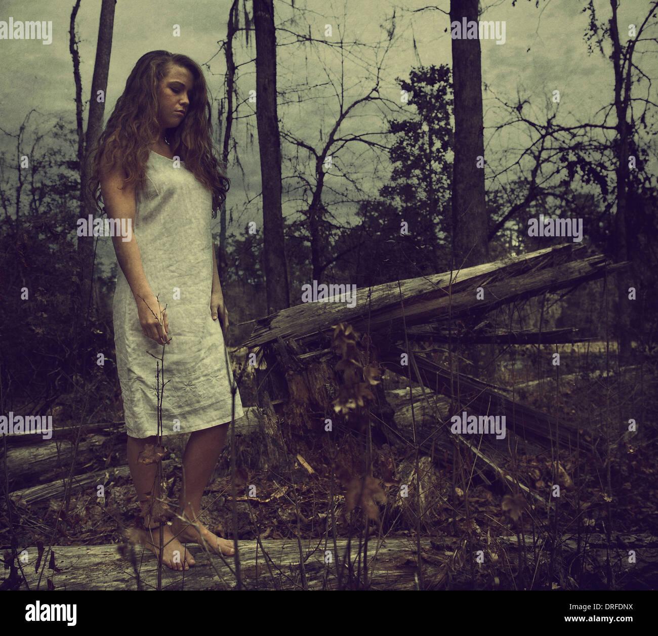 Frau im weißen Kleid stehen in Wäldern mit umgestürzten Bäumen Stockbild