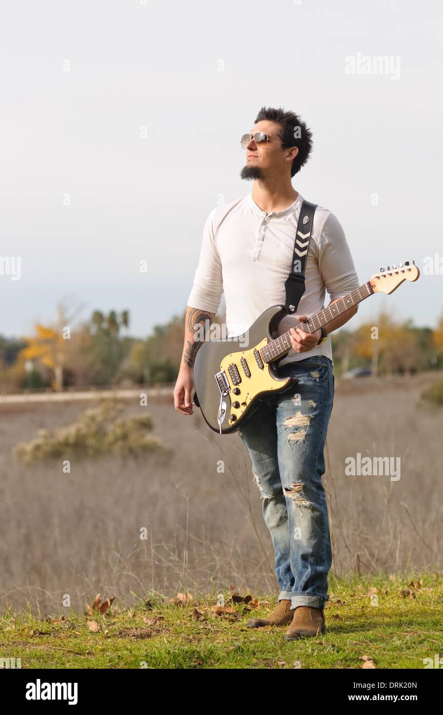 Ein Mann, Rock-Musiker spielen seine e-Gitarre im freien wegschauen Stockbild