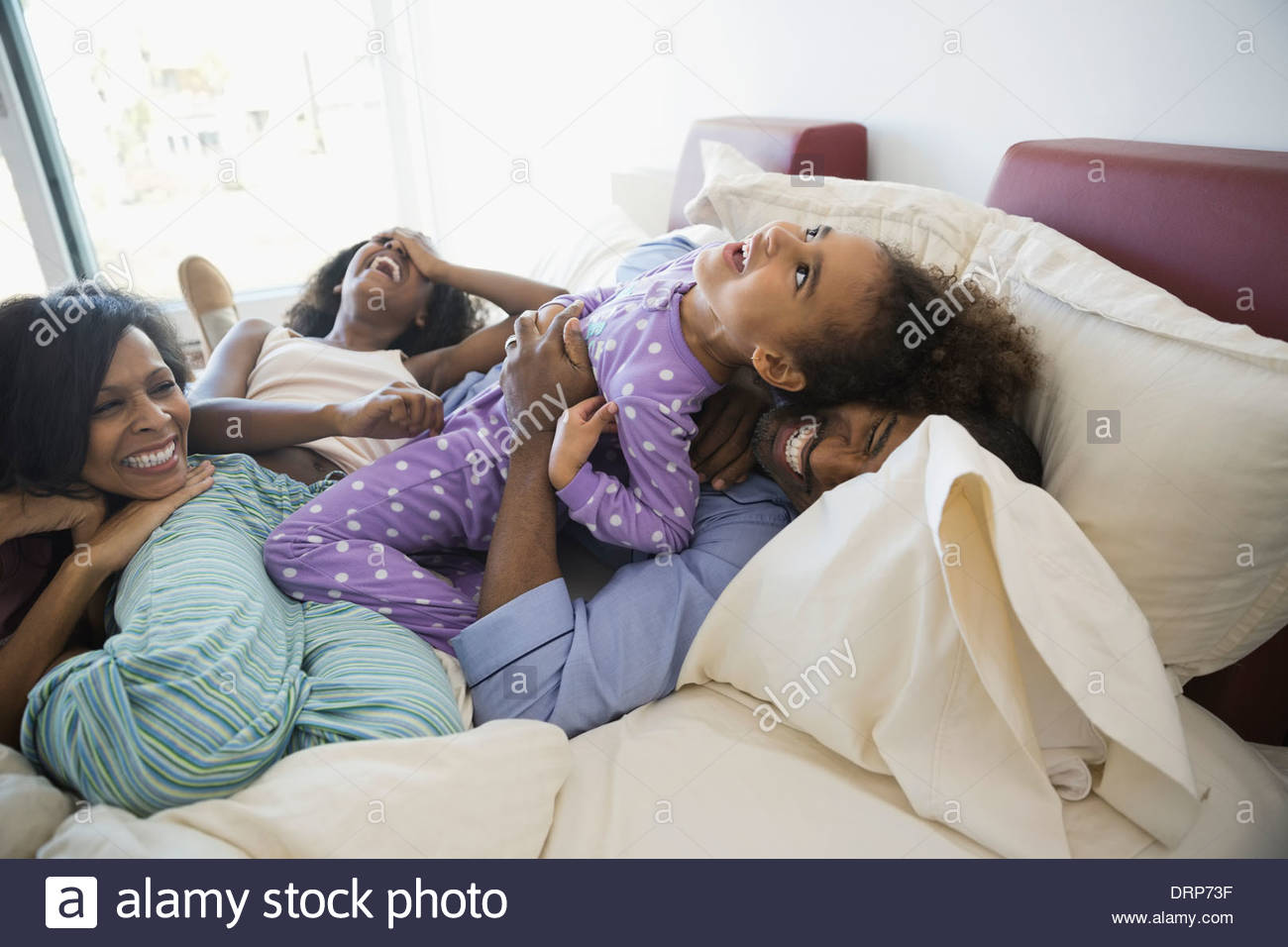 Spielerische Familie im Bett Stockfoto
