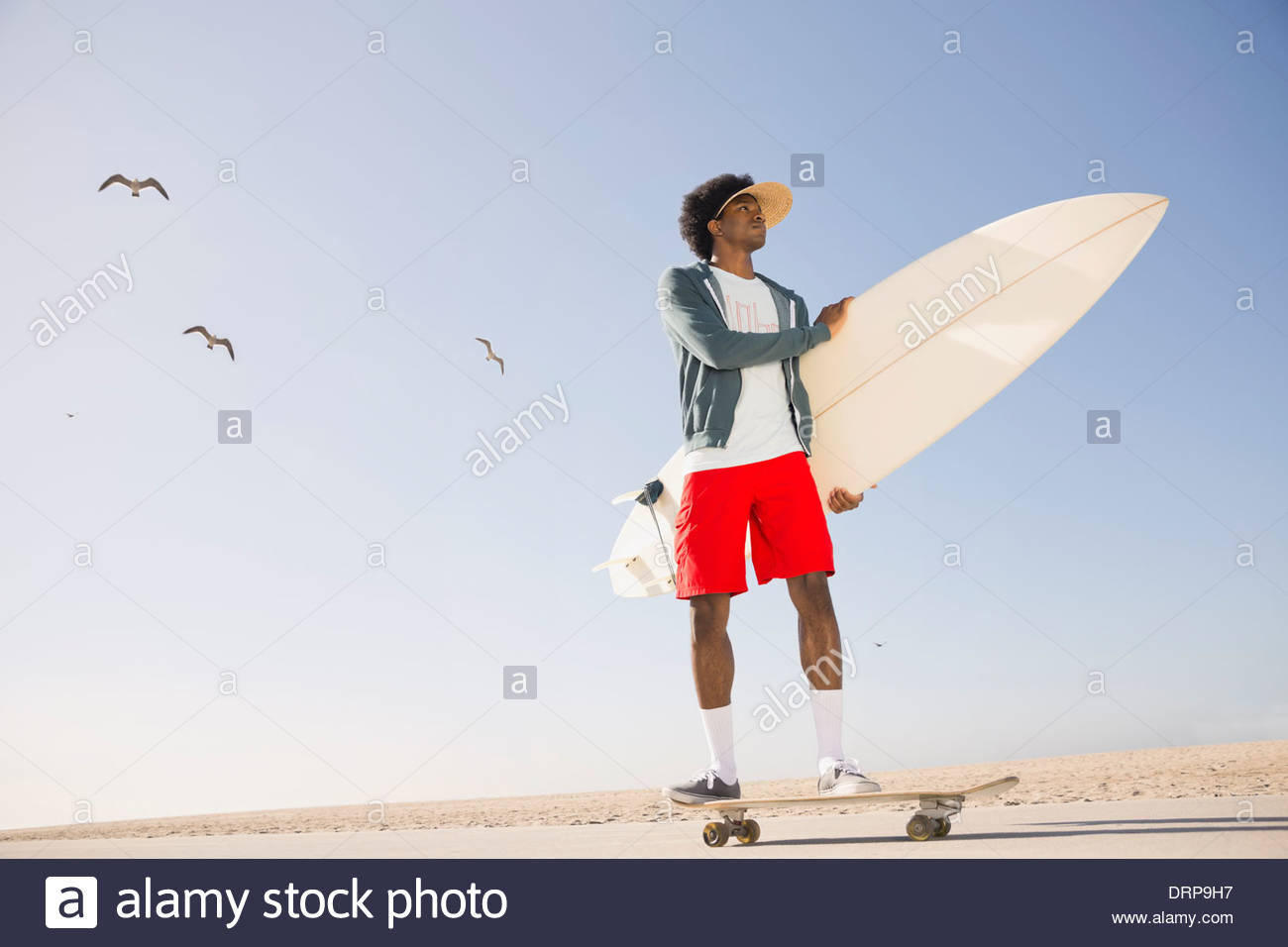 Männliche Surfer Skateboard am Strand Stockbild