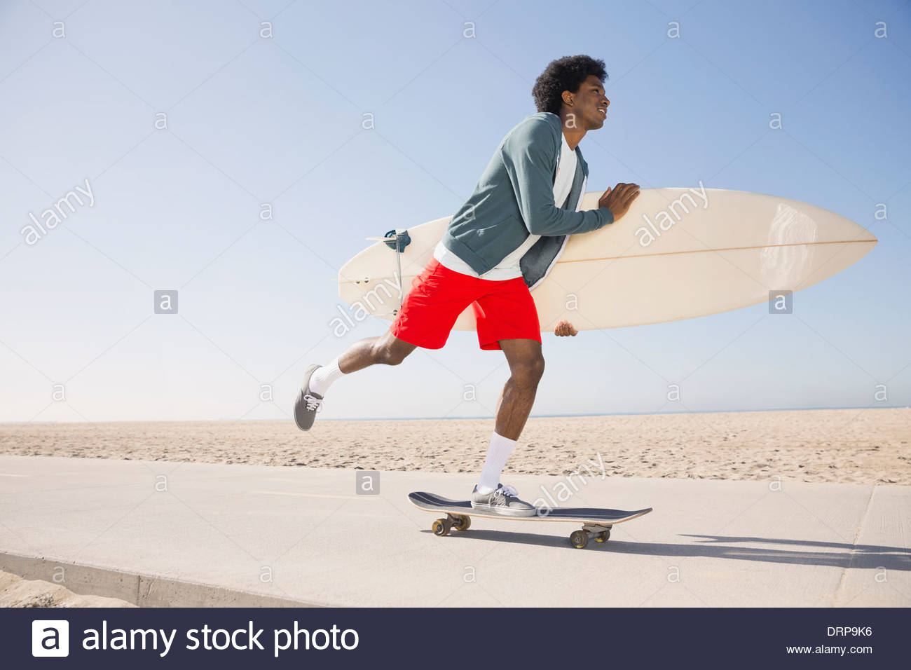 Surfer am Strand skateboarding Stockbild