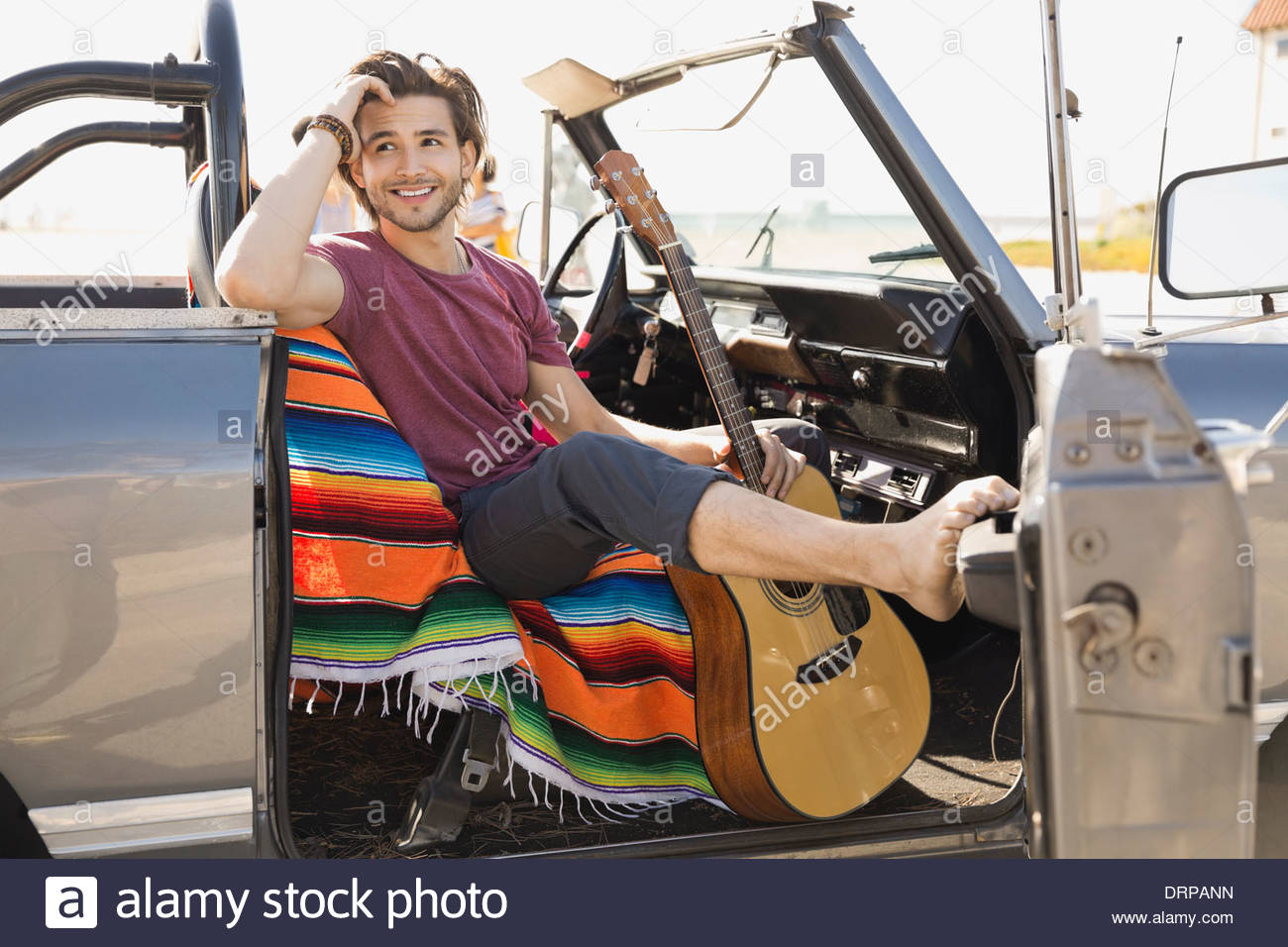 Mann mit Gitarre im Off-Road-Fahrzeug sitzen Stockbild
