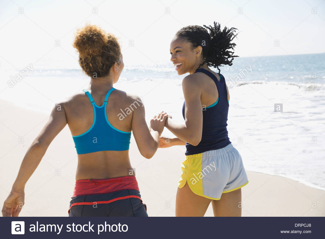 Freundinnen am Strand joggen Stockbild