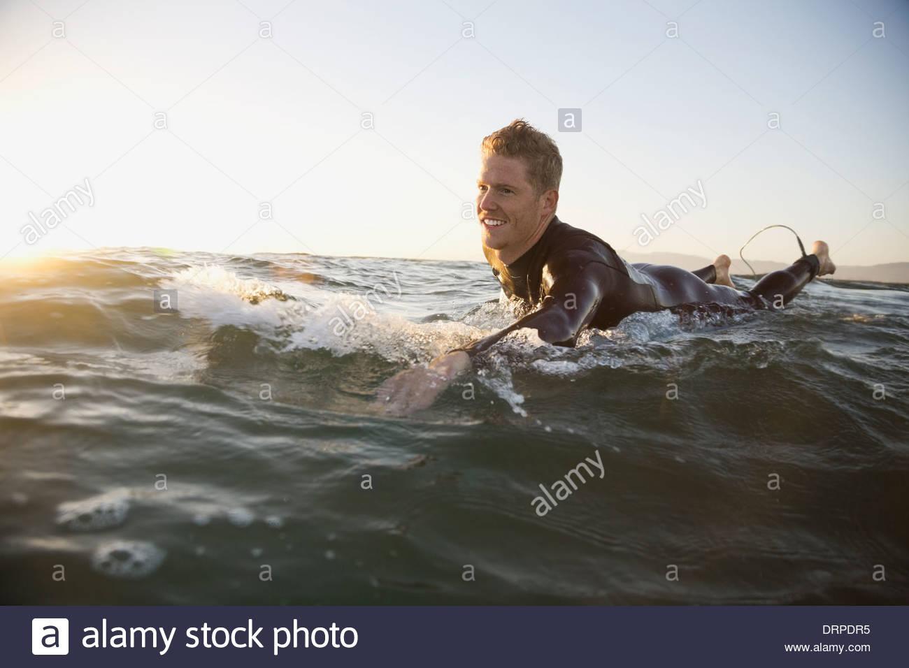 Mann auf Surfbrett paddeln Stockbild