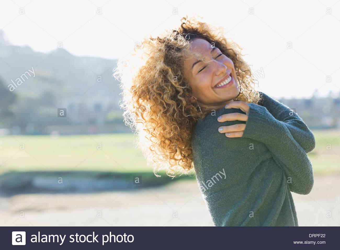 Lächelnde Frau mit Augen geschlossen im freien Stockbild
