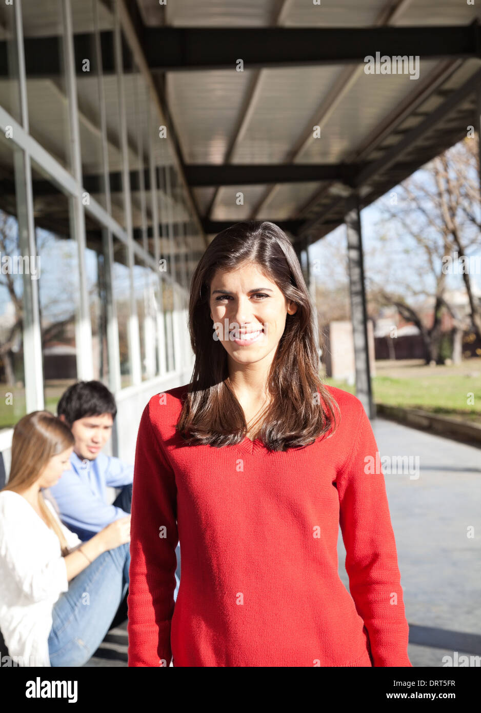 Frau lächelnd mit Studenten im Hintergrund auf dem Campus Stockbild