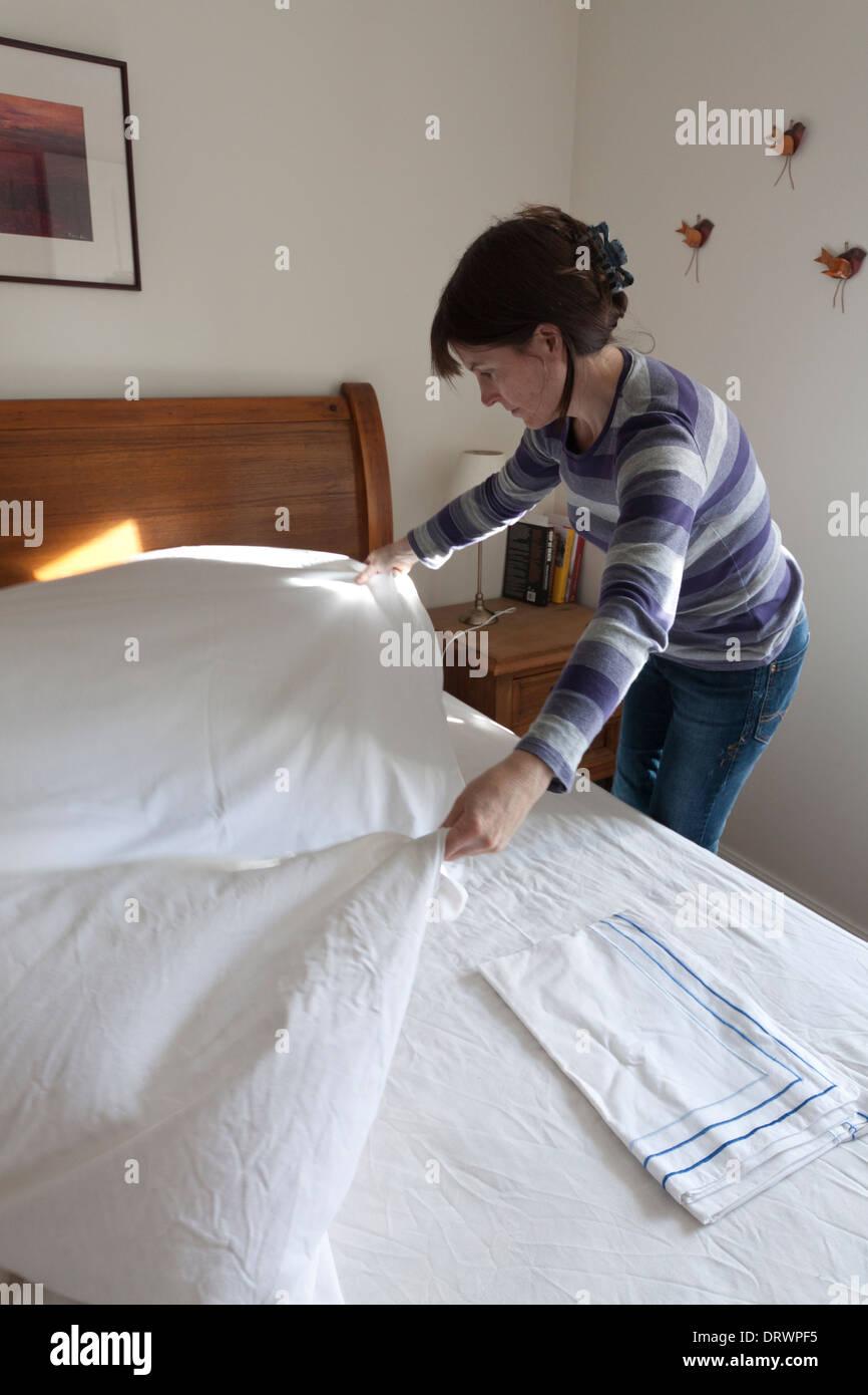 Frau, die ein Bett vorbereiten Stockbild