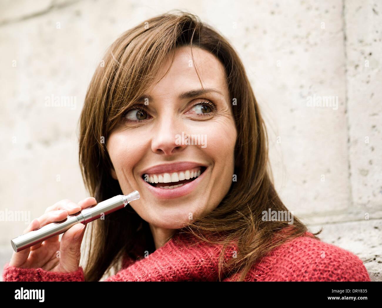 Frau rauchen elektronische Zigarette, Lächeln Stockbild