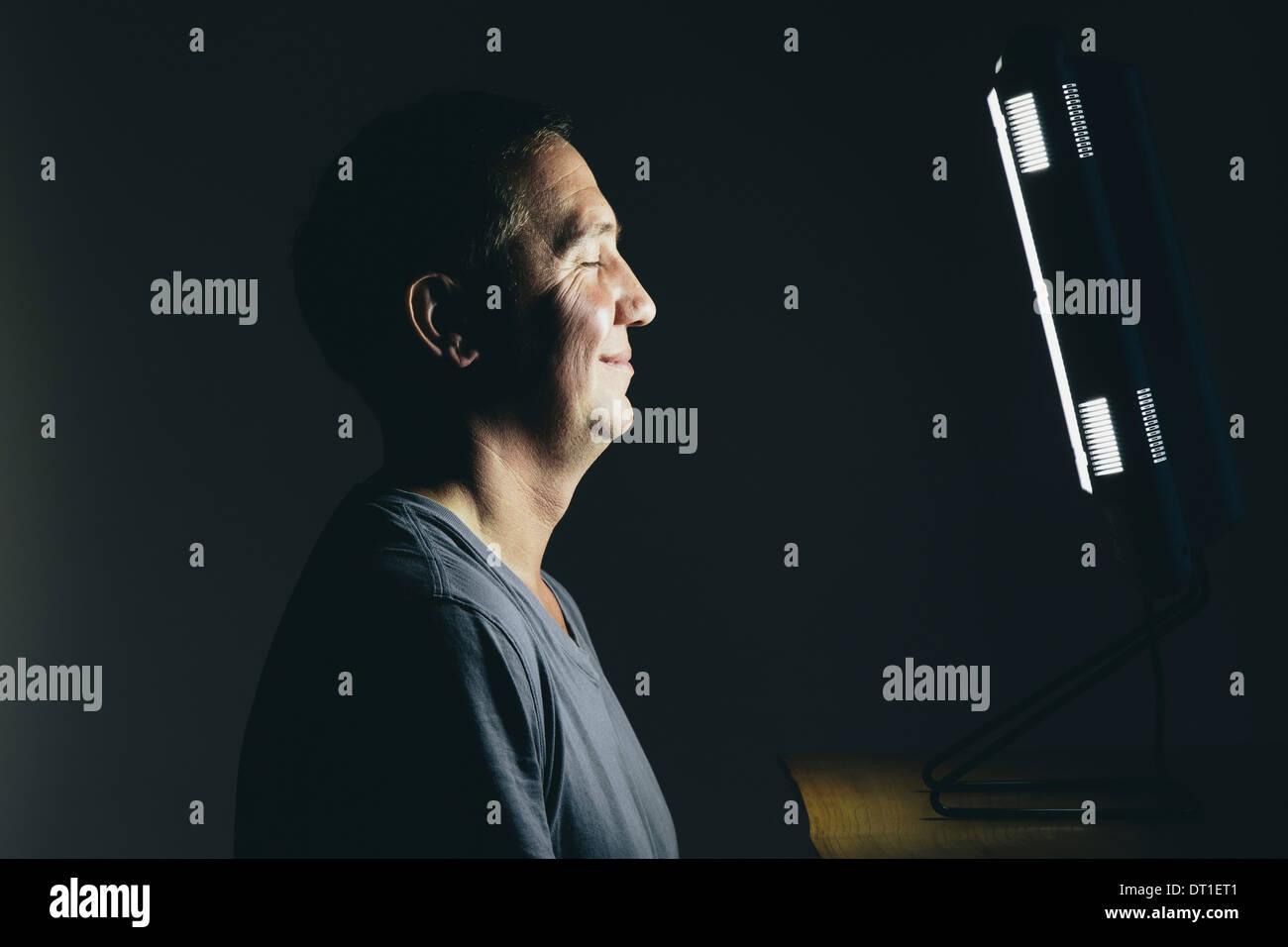 Lächelnd Mitte im Alter Mann sitzt vor einer Lichttherapie Box Behandlung von Winterdepressionen leidet Stockbild