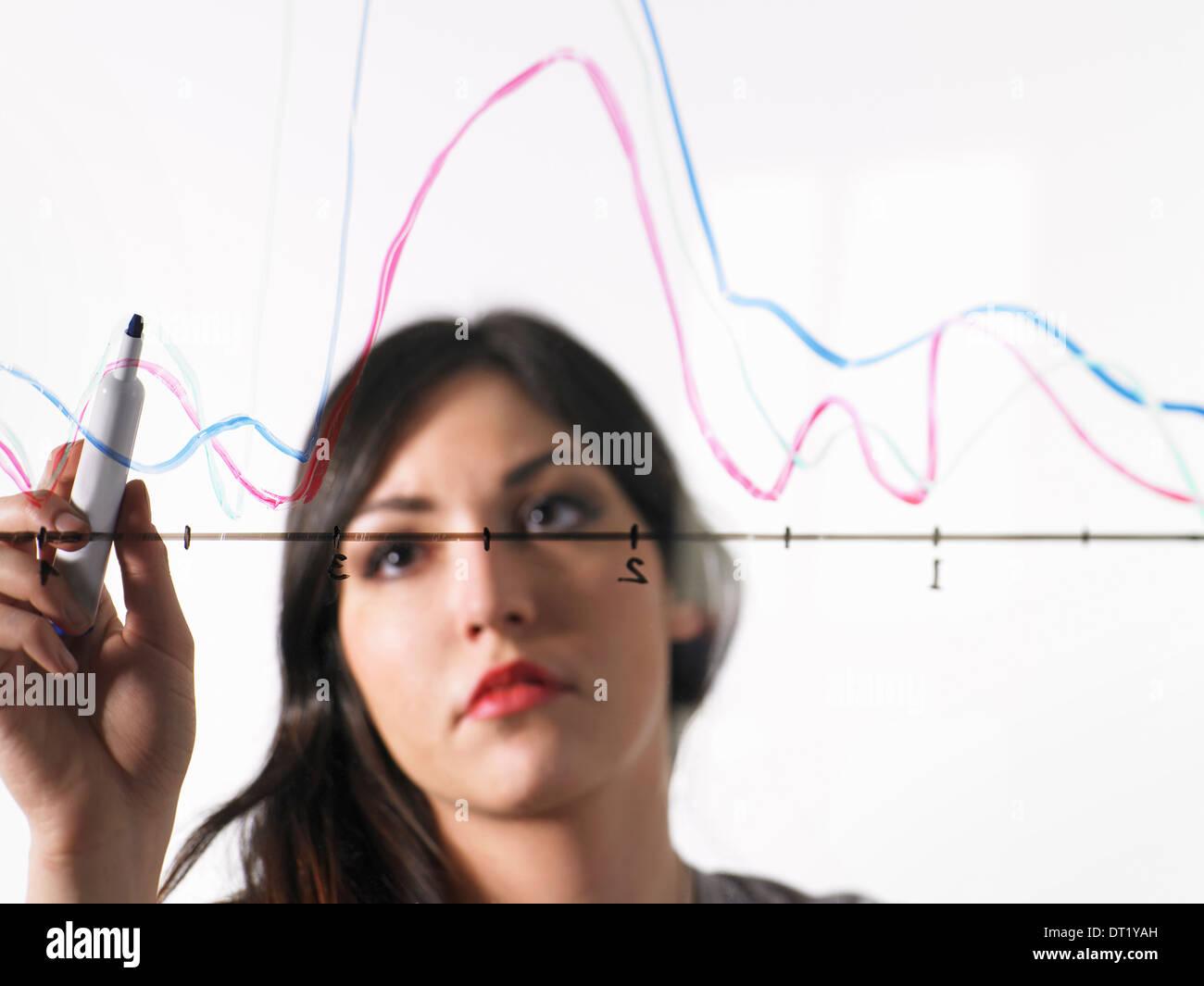 Eine junge Frau, die farbige Grafik Linien über eine Grafik Illustration auf einen durchsichtigen Oberfläche Stockbild