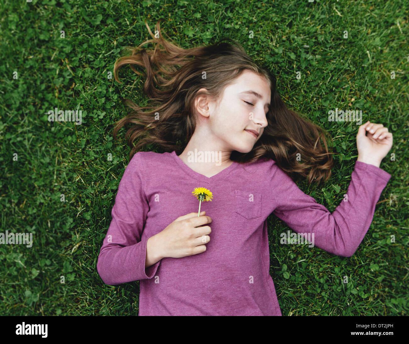 Ein Zehn Jahres altes Mädchen liegen auf dem Rasen mit ihren Augen geschlossen, die eine Löwenzahn Blume Stockbild