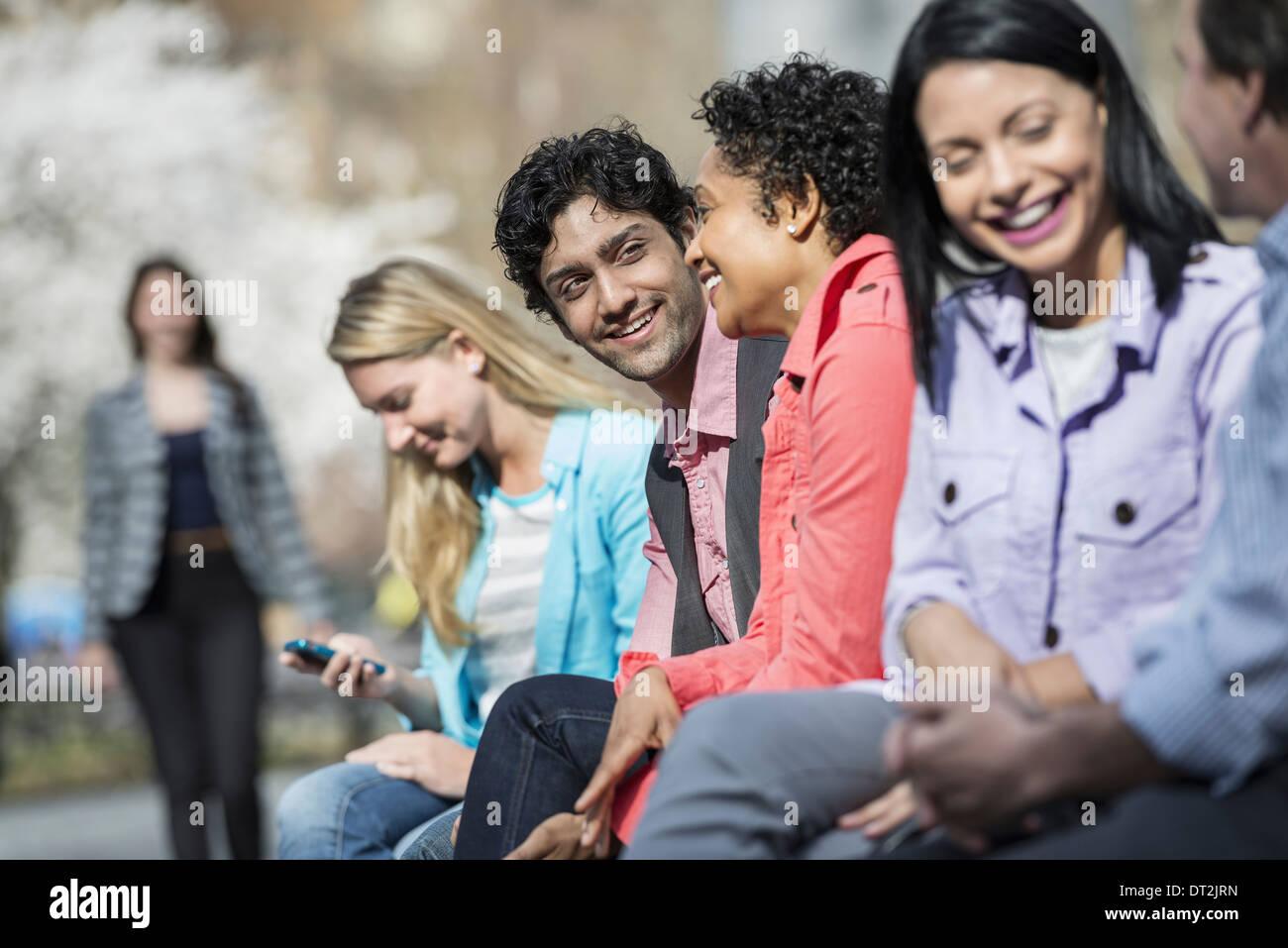 Fünf Leute sitzen in einer Reihe im park Stockbild