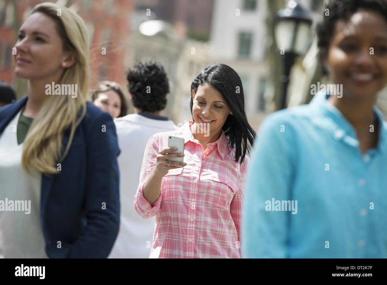 Drei Frauen eine Überprüfung ihrer mobilen Phon zu parken Stockbild