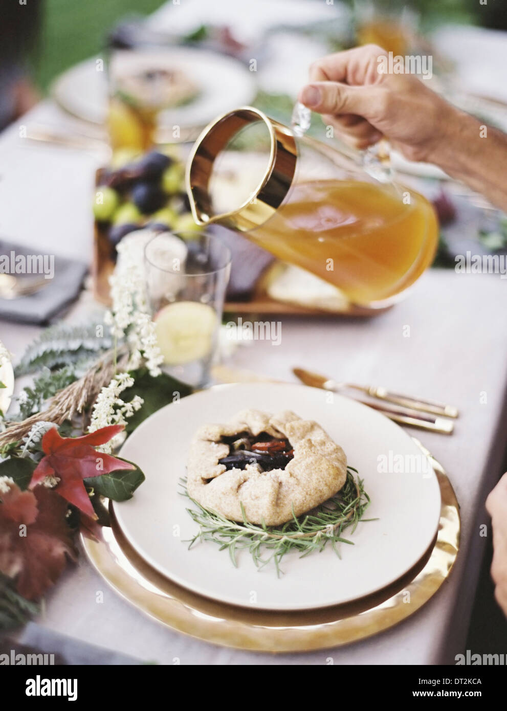 Eine Feier Mahlzeit mit gedeckten Tisch und grünen Dekorationen A Person Getränke in Gläser gießen Stockbild