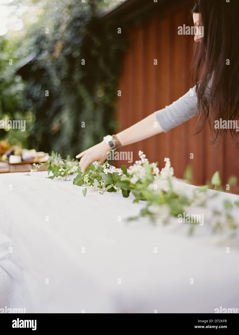 Eine Frau mit langen Haaren vom Tisch gelegt außerhalb mit einem weißen Tuch und zentrale Laub Tisch Dekoration Stockbild