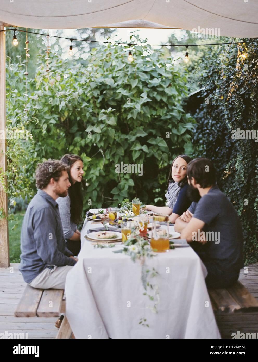 Vier Personen sitzen an einem Tisch im Garten Gedecke und Dekorationen auf ein weißes Tischtuch zwei Männer Stockbild