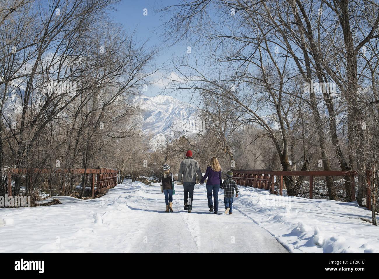 Winterlandschaft mit Schnee auf dem Boden A Familie Erwachsene und zwei Kinder, die eine leere Straße hinunter Stockbild