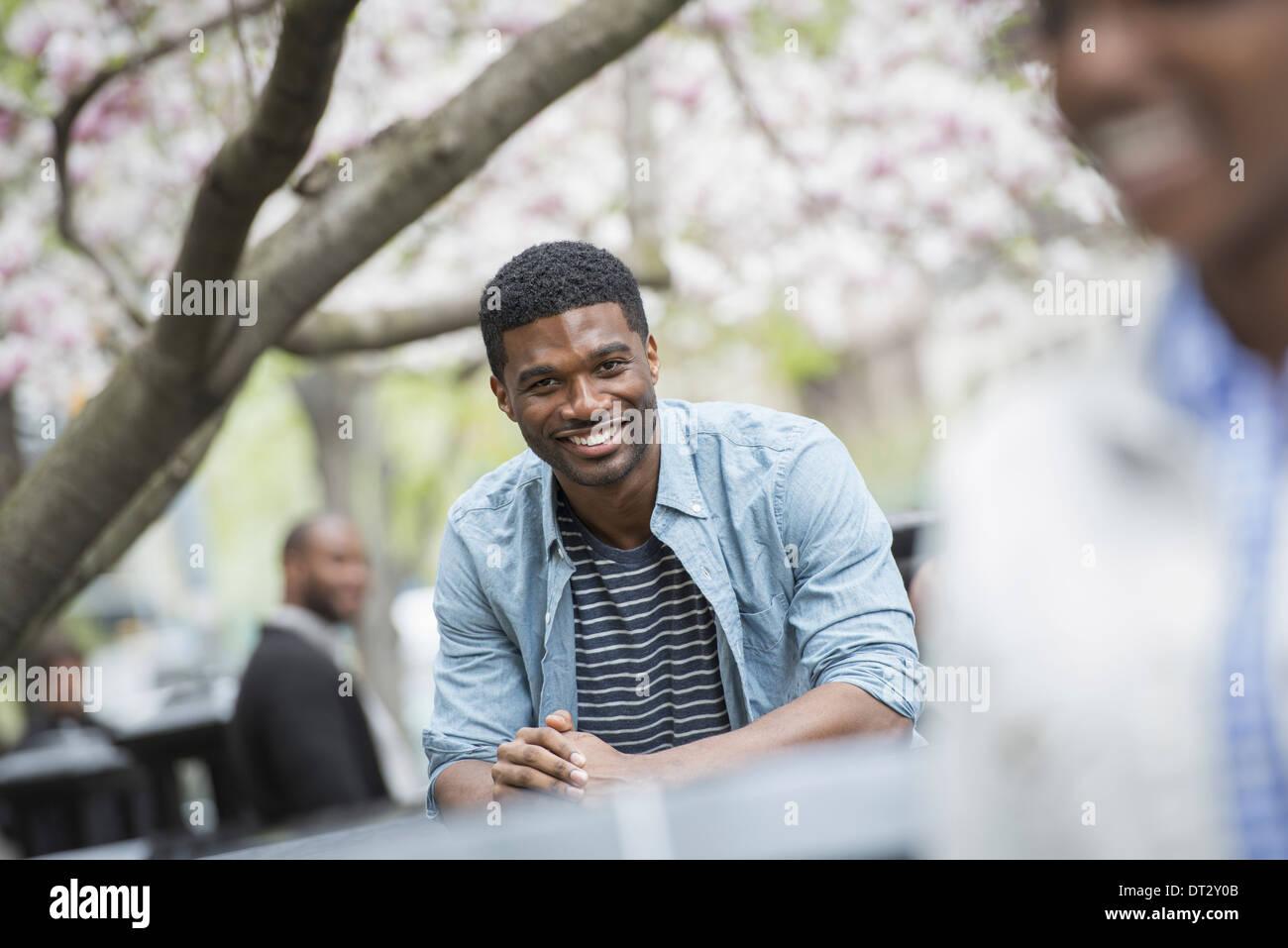 Ein Mann sitzt an einem Tisch Lächeln einer Frau im Vordergrund Stockbild