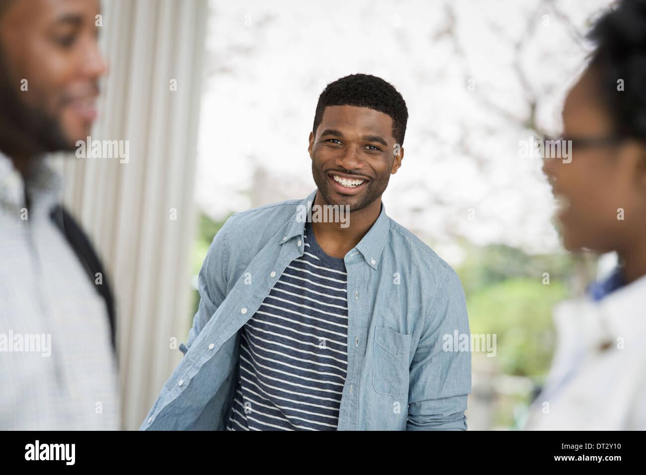 Ein Mann schaut in die Kamera mit zwei Personen im Vordergrund Stockbild