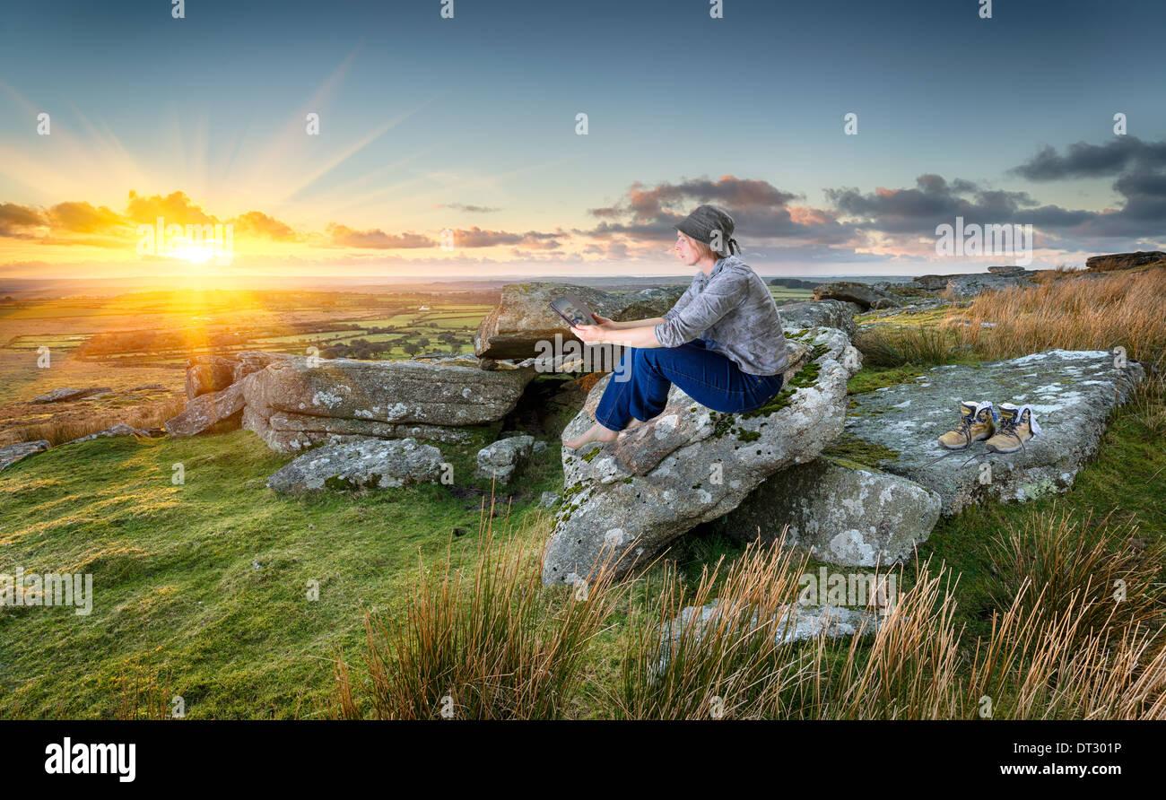 Frau, Wandern, entspannen und unter Verwendung eines Tablet PCs bei Sonnenuntergang auf einem felsigen Tor auf Bodmin Stockbild