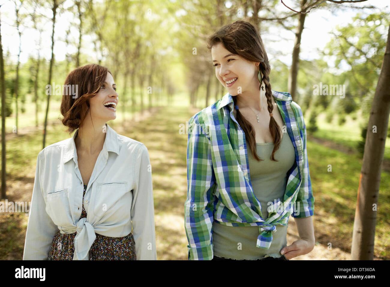Zwei junge Frauen, die hinunter einer Allee von Bäumen Stockbild